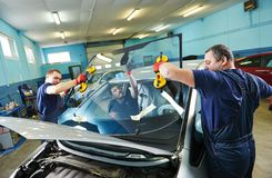 Windshield windscreen replacement. Automobile glaziers workers replacing windscreen or windshield of a car in auto service station garage