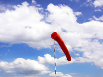 Windsock. Red windsock on the blue sky with white clouds Stock Photos