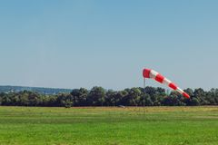 Windsock as a gauge for winds, wind vane on aerodrome airfield on an air show. Windsock as a gauge for winds, wind vane on the aerodrome airfield on an air show royalty free stock photo