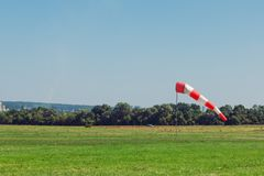Windsock as a gauge for winds, wind vane on aerodrome airfield on an air show. Windsock as a gauge for winds, wind vane on the aerodrome airfield on an air show stock photo