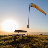 Windsock and bench to watch paragliders Royalty Free Stock Image