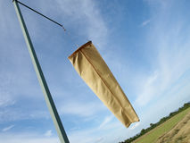 Windsock and Light Aircraft Runway. Windsock at an Oblique Angle with a Light Aircraft Runway and Clear Blue Sky in the Background Stock Photo