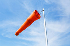 Windsock. Orange color windsock use as wind direction and speed indicator on blue sky royalty free stock photography