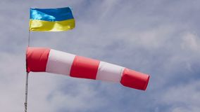 Windsock and Ukrainian flag in the sky on airport. Wind direction indicator at the airport stock footage