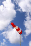Windsock (vertical). Red and white windsock blows against a blue sky Royalty Free Stock Images