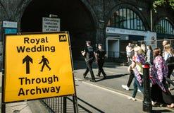 Royal Wedding Street traffic sign. WINDSOR, BERKSHIRE, UNITED KINGDOM - MAY 19, 2018: Crowd walking near Royal Wedding road sign on the day of the royal wedding Royalty Free Stock Photo
