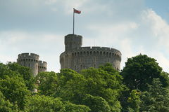 Windsor Castle above tree tops. Windsor Castle is an official residence of The Queen and the largest occupied castle in the world Royalty Free Stock Image