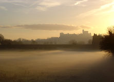 Windsor castle at dawn. Windsor Castle, Windsor, England at dawn looking over mist filled fields Royalty Free Stock Image