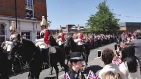 British traditional Royal Guards on horses. WINDSOR, UNITED KINGDOM - MAY 19, 2018: Crowd admiring the Royal Guards on horses after newlywed carriage in Windsor stock video