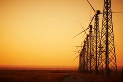 WindStromerzeugung, Windkraftanlagen auf Ackerland mit Sonnenuntergang Lizenzfreie Stockfotos