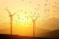 Windstromgeneratoren auf dem Hintergrund von Schattenbildern von Bergspitzen und von Menge von Vögeln Einfachheit und minimale Li lizenzfreie stockfotos
