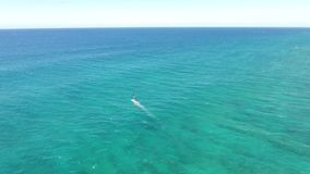 Windsurder gliding slowly in calm waves of turquoise blue Pacific ocean water Hawaii in amazing 4k aerial drone seascape stock video