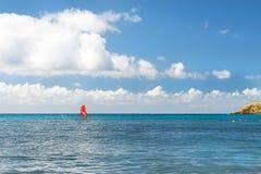Windsurf с красным ветрилом Водные виды спорта на каникулах Стоковые Фото