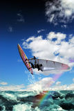 Windsurf. A man with his windsurfing board, jumps up on waves, whereas a rainbow crosses the image Royalty Free Stock Photography