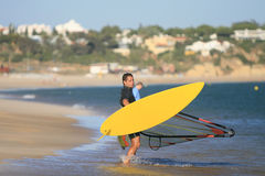 Windsurf. Summer sports: windsurfer with yellow board on the beach, Algarve, south of Portugal Stock Image