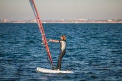 Windsurf cerca de la ciudad de Anapa Realizando diversos trucos en a windsurf al resbalar en un mar imagen de archivo
