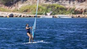 Windsurf de la mujer en aguas azules foto de archivo