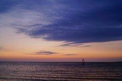 Windsurf en la puesta del sol en el mar Imágenes de archivo libres de regalías