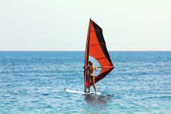Windsurf - surfer girl. On blue sea surface stock photo