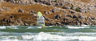 Windsurfer плавает быстро через зеленые волны Стоковое Изображение