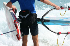 Windsurfer. Close up of a windusrfer as he walks out into the water royalty free stock photo