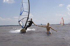 Windsurfer atteignant pour l'amie Photographie stock libre de droits