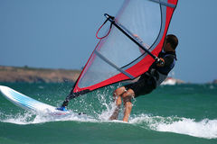 Windsurfer with bright colored sail and board. Royalty Free Stock Photography