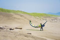 A windsurfer carries his board away from the beach Royalty Free Stock Image