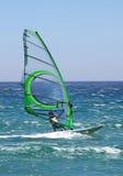 Windsurfer con esperienza che accelera lungo il mare blu pieno di sole che dà una sensibilità reale del movimento. Fotografia Stock