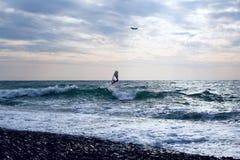 Windsurfer die door golvende overzees bij vliegende vliegtuigenachtergrond surfen royalty-vrije stock fotografie
