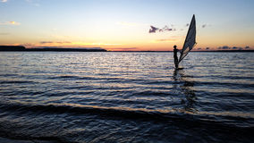 Windsurfer die in het meer bij zonsondergang varen Stock Afbeelding
