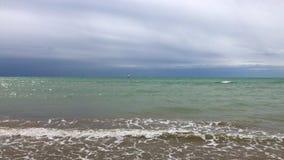 Windsurfer en la línea de mar, cielo nublado de las ondas suaves