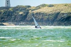Windsurfer genießt den Strand bei Newborough Waren mit der Insel von Llanddwyn im Hintergrund, Insel von Anglesey lizenzfreie stockfotografie