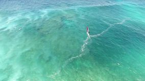Windsurfer gliding slowly in calm summer wave of turquoise blue ocean water in Hawaiian seascape in 4k aerial drone view. Windsurfer gliding slowly in calm stock footage