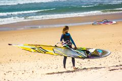 Windsurfer holding the sailboard ready to start her training Stock Image