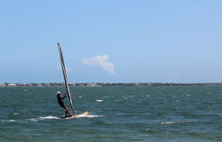 WINDSURFER ON INDIAN RIVER LAGOON IN STUART,FLORIDA. Windsurfer surfing on the INDIAN RIVER LAGOON in STUART, FLORIDA on a clear windy day with deep blue water Royalty Free Stock Images