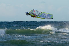 Windsurfer in jumping. Windsurfer in the waves doing a backloop Royalty Free Stock Photo