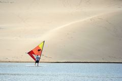 Windsurfer on Lagoon. Windsurfer with a colorful sail on a lagoon with a huge sand dune in the background Royalty Free Stock Photography