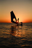 Windsurfer learning silhouette against sun Royalty Free Stock Images