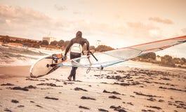 Windsurfer mit Brett auf Strand-Küstenrückseitenansicht Seewindsurfen-Sport Stockfotografie