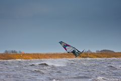 Windsurfing high jump on a lake. Windsurfer on the Neusiedlersee Lake Neusiedl performing a jump in strong wind and waves. Stormy cold weather with dark sky in Royalty Free Stock Photo