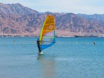 Windsurfer op de raad met een zeil beweegt zich op het Rode Overzees Achtergrond - bergen stock foto's
