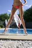 Windsurfer in pool. Windsurfer in a pool seen throught the legs of a model in a bikini Royalty Free Stock Photos