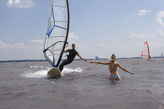 Windsurfer reaching for girlfriend Royalty Free Stock Photography