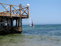 Windsurfer with a red sail near the pier. Near the shore in the sea the surfer sails on the waves Stock Photo