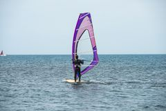 A windsurfer rides on the sea in calm, light wind stock image
