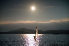 Windsurfer sailing into breeze Shot with gentle filter. Strong sun makes reflections. Stock Images