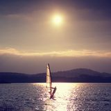 Windsurfer sailing into breeze Shot with gentle filter. Strong sun makes reflections. Stock Photo