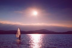 Windsurfer sailing into breeze Shot with gentle filter. Strong sun makes reflections. Royalty Free Stock Image
