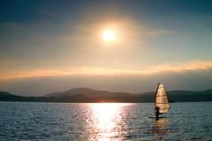 Windsurfer sailing into breeze Shot with gentle filter. Strong sun makes reflections. royalty free stock photo